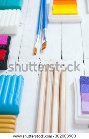 plasticine blocks, ink pads and pencils, brushes on white wood table