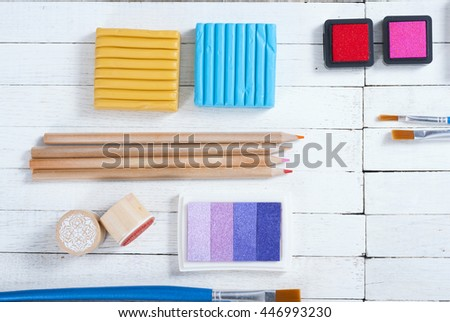 plasticine blocks, ink pads and pencils, brushes on white wood table - stock photo