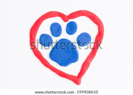 Plasticine paw and heart - Stock Image macro. - stock photo