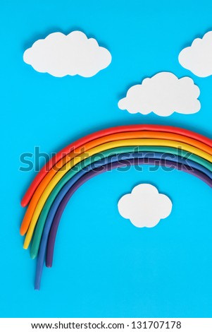 Plasticine rainbow near white paper clouds on blue background - stock photo