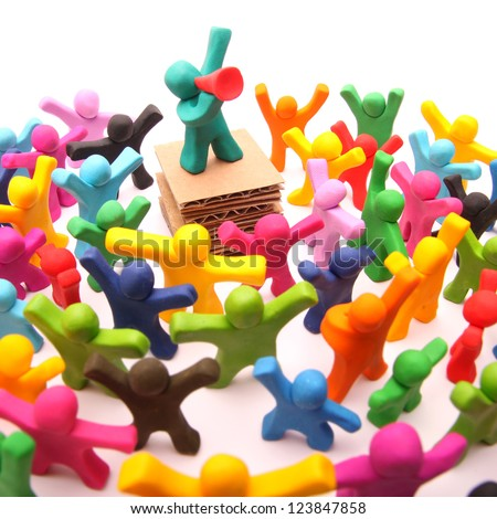 plasticine speaker with bullhorn speaking to a colorful crowd of plasticine people