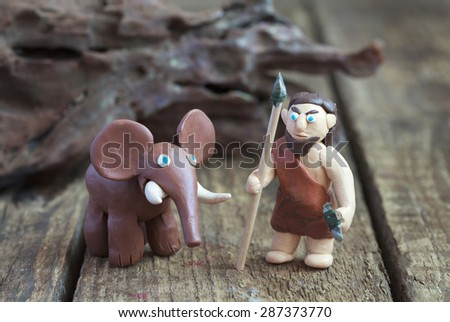 Plasticine world - a caveman with a spear and a stone ax and a mammoth, selective focus - stock photo