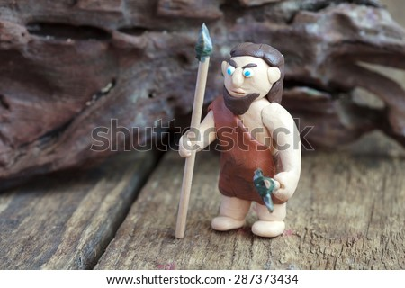 Plasticine world - a caveman with a spear and a stone ax, selective focus - stock photo