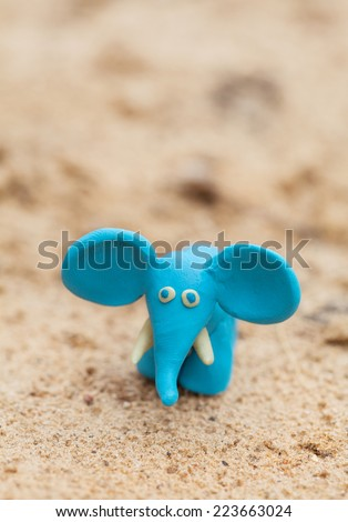 Plasticine world - little homemade blue elephant on a sand background , selective focus and place for text - stock photo