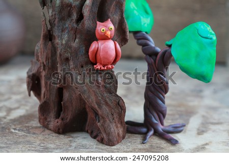 Plasticine world - little homemade brown owl with yellow eyes sitting on a rock, near old tree on a wooden background, selective focus - stock photo