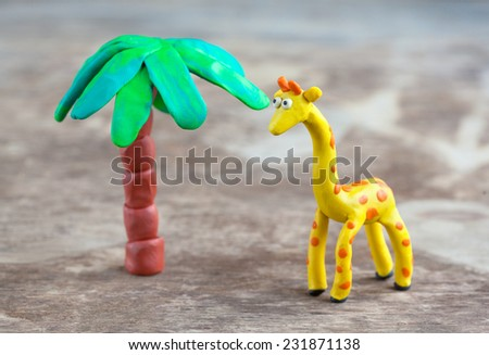 Plasticine world - little homemade yellow giraffe with orange spots and palm on a wooden background, selective focus and place for text  - stock photo
