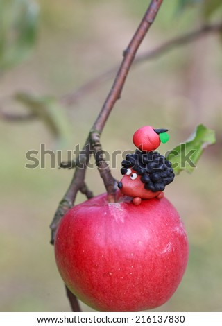 Plasticine world - small homemade hedgehog sitting on apple with red apple on his back, selective focus on the hedgehog, place for text - stock photo