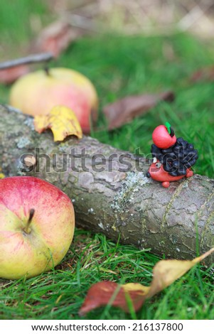 Plasticine world - small homemade hedgehog sitting on tree trunk with red apple on his back on a green meadow surrounded apples, selective focus on the hedgehog  - stock photo