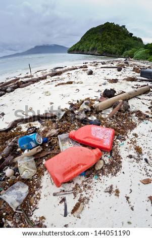 Plastics and other refuse has washed ashore a remote island in the tropical western Pacific region.  Plastics, in particular, are a serious threat to the marine ecosystem. - stock photo