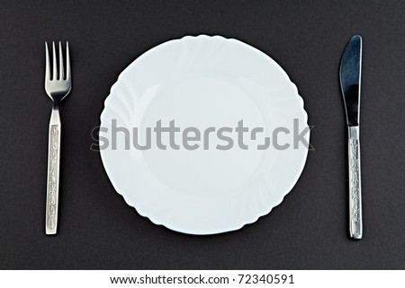 Plate a plug and a knife against a dark background - stock photo