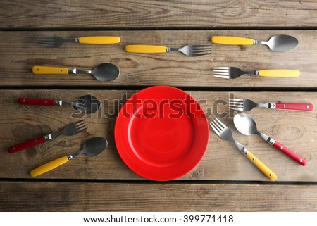 Plate and colorful flatware on wooden table, top view - stock photo