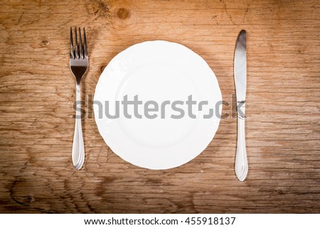 plate and cutlery on a wooden old table