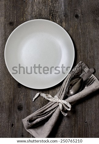plate and linen napkins on wooden background in rustic style (dark) - stock photo