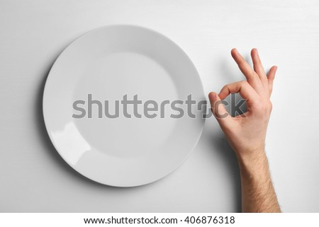 Plate and male hand showing OK sign, isolated on white - stock photo