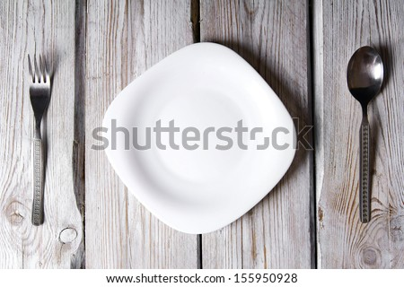Plate and tablewares. On wooden board. - stock photo
