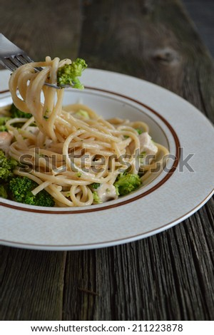 Plate broccoli and Alfredo sauce. Background from old boards