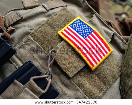 Plate carrier (bulletproof vest) with USA flag and M4 magazines - stock photo
