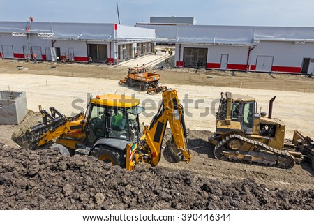 Plate compactor is mounted to the truck, compacting soil for the new road construction site. - stock photo
