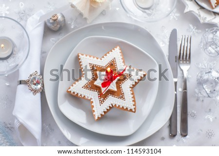 Plate for Christmas evening decorated with small present and gingerbread cookie - stock photo