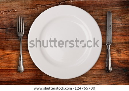 Plate, fork and knife on wooden table - stock photo