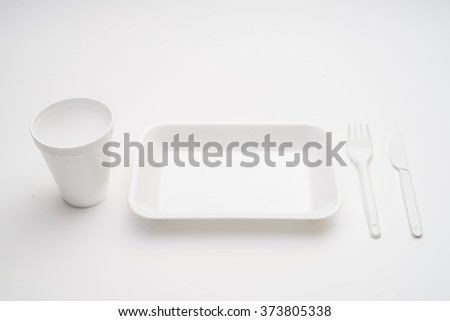 Plate, fork and knife with white plate on white background - stock photo