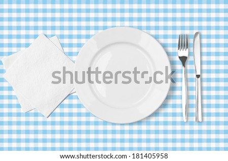 plate, fork, knife and napkin over blue checked fabric tablecloth top view - stock photo