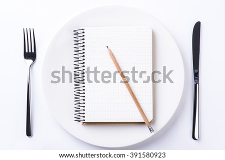 Plate, fork, knife, pencil and notebook tape on light wooden table
