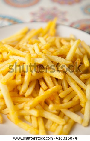 Plate full of crispy fries on a table with tablecloth - stock photo