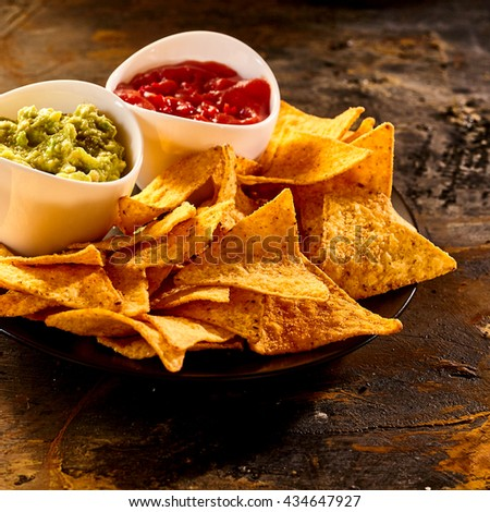 Plate full of guacamole, salsa and nacho chips close up on old worn out dark stained table