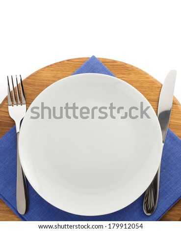 plate, knife and fork at cutting board on white background
