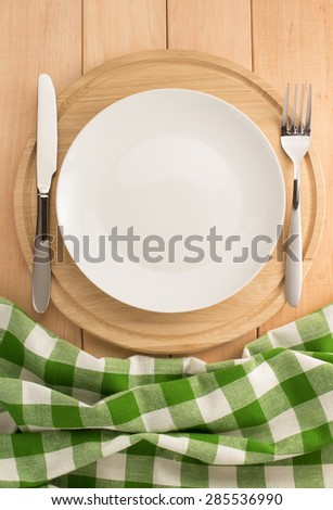 plate, knife and fork at cutting board on wooden background - stock photo