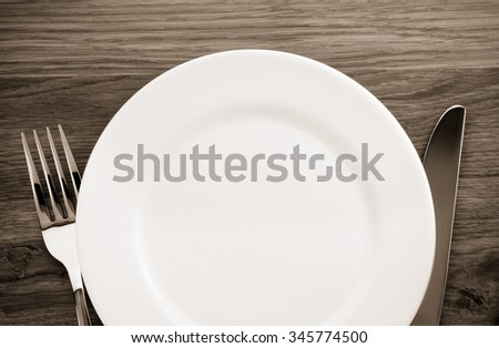 plate, knife and fork at cutting wooden board - stock photo