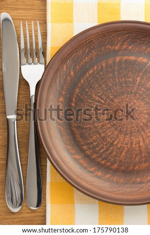 plate, knife and fork at napkin on wooden background - stock photo