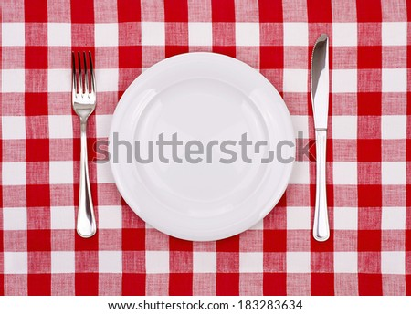 Plate knife and fork on a checkered tablecloth - stock photo