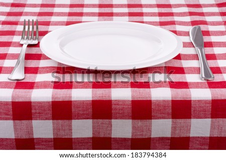 Plate knife and fork on a checkered tablecloth