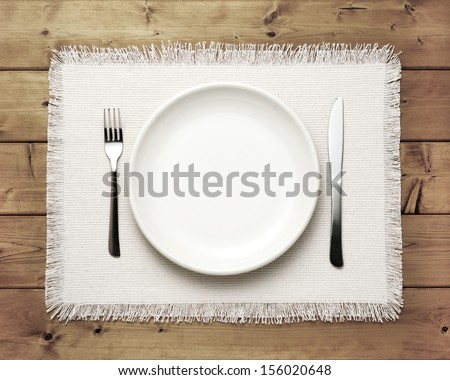 plate knife and fork on wooden table - stock photo