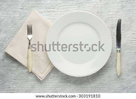 plate knife and fork on wooden table. - stock photo