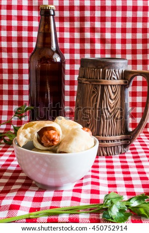Plate Mini hot dogs homemedae (sausage in pastry) on napkin with a bottle of dark beer and earthenware mug on a plaid background - stock photo