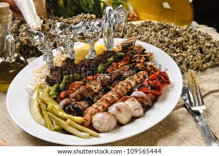 Plate of Arabic oriental barbeque, made of different kinds of meat,backed with vegetables. - stock photo