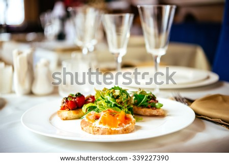 Plate of assorted Italian appetizer bruschetta with chopped vegetables, salmon and meat on ciabatta bread, garnished with green mix salad - stock photo