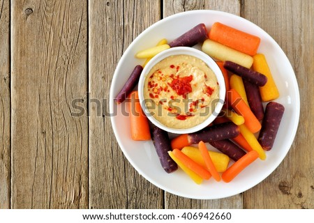 Plate of baby rainbow carrots with hummus dip, overhead view on a rustic wooden background