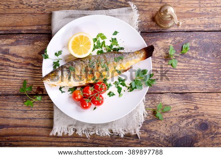 plate of baked sea bass on wooden table - stock photo