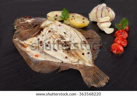 Plate of baked turbot fish with potato slices, seasoned with garlic, cherry tomatoes, parsley, thyme, red and black pepper grains and black salt. - stock photo
