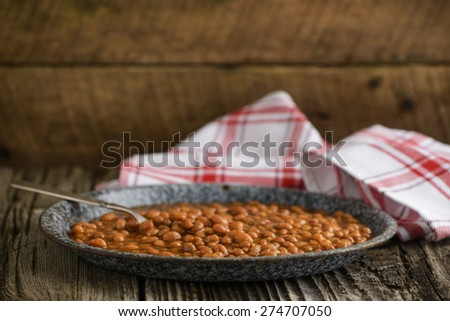 Plate of beans with pork in a rustic setting. - stock photo