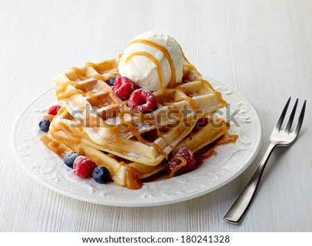 Plate of belgian waffles with ice cream, caramel sauce and fresh berries - stock photo