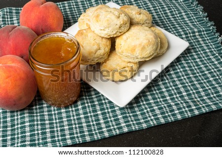 Plate of biscuits with peach jam or jelly and peaches - stock photo