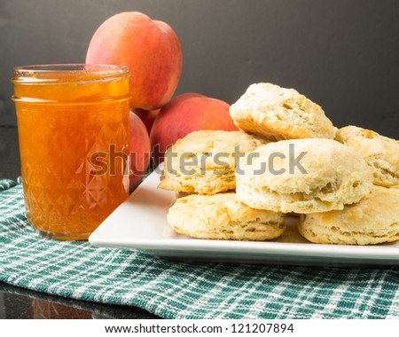Plate of biscuits with peaches and peach jam - stock photo
