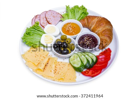 Plate of breakfast with croissant, boiled egg, meat and cheese in big white plate, isolated with clipping path - stock photo