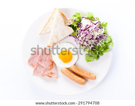 Plate of breakfast with fried eggs, toast, ham, sausage and vegetables on white background - stock photo