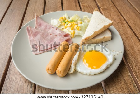 Plate of breakfast with fried eggs, toast, ham, sausage and vegetables on  wooden table